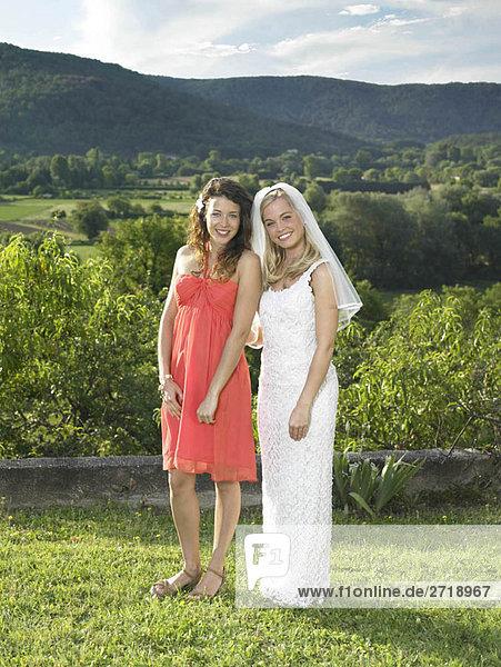 Braut und Brautjungfer im Garten