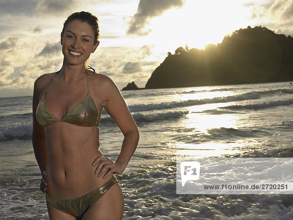 Junge Frau am Strand bei Sonnenuntergang