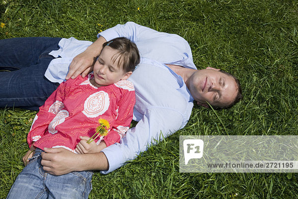 Father and daughter (6-7) relaxing in the meadow,  elevated view