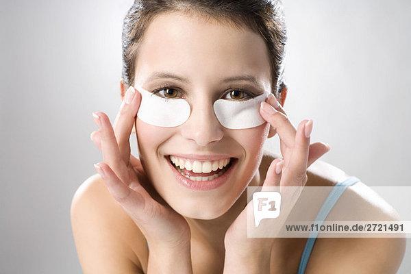 Junge Frau mit Augenkissen  lächelnd  Nahaufnahme