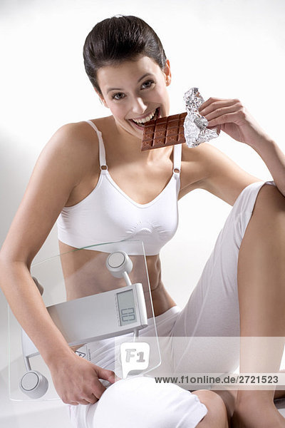 Young woman holding scales  biting into chocolate bar