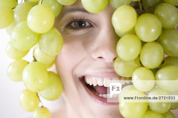 Junge Frau mit Trauben über dem Kopf  lächelnd
