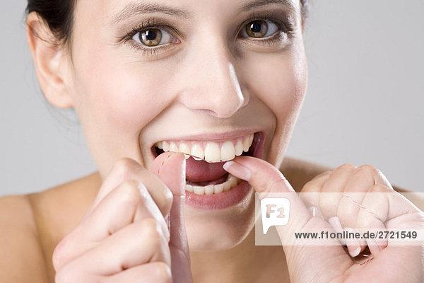 Junge Frau mit Zahnseide  Nahaufnahme