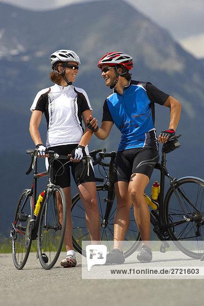 Deutschland  Bayern  Mittenwald  Paar mit Mountainbikes  sprechend