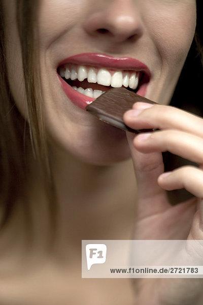 Junge Frau  die Schokoladenbonbons in den Mund nimmt  Porträt
