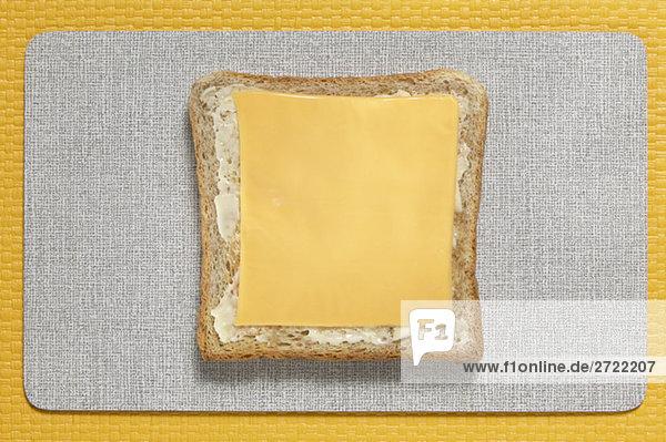 Brotscheibe mit Schmelzkäse-Scheiben  erhöhte Ansicht