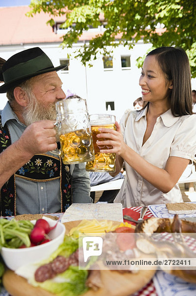 Upper   Asian woman and bavarian man toasting each other