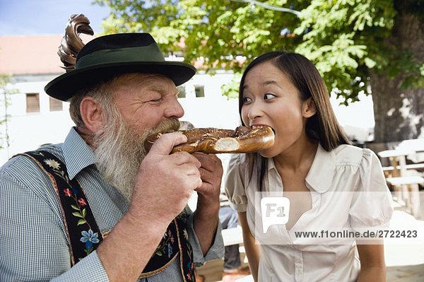 Oberer  n Mann und asiatische Frau im Biergarten essen Brezel  Porträt