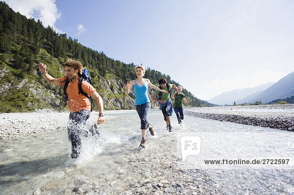 Germany  Bavaria  Tölzer Land  Young friends running through river