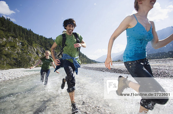 Germany  Bavaria  Tölzer Land  Young people running through river