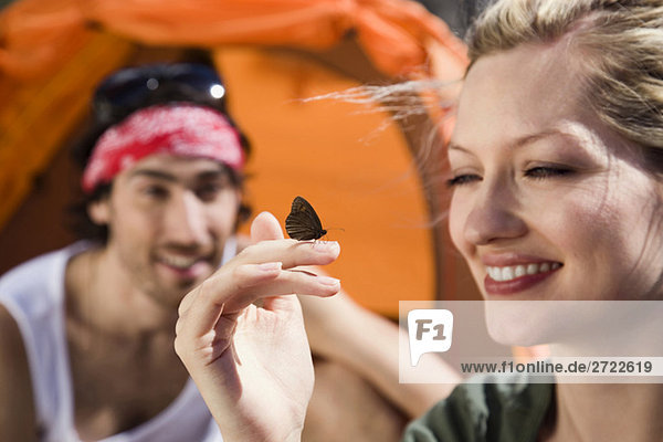 Young couple camping  butterfly resting on woman's hand