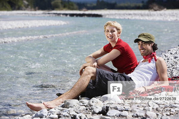 Germany  Bavaria  Tölzer Land  Young couple sitting on riverbank