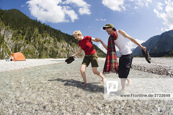 Germany  Bavaria  Tölzer Land  Young couple walking through river  holding hands  tent in background