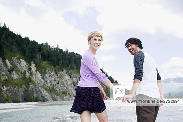 Germany  Bavaria  Tölzer Land  Young couple walking hand in hand near Isar rivee