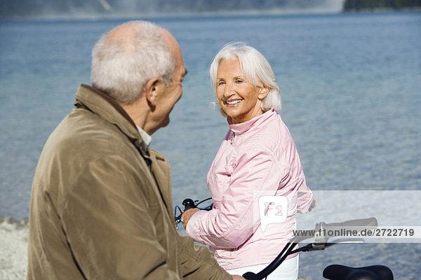 Deutschland  Bayern  Walchensee  Seniorenpaar beim Radfahren am Seeufer