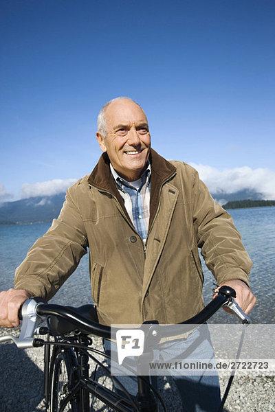 Senior Mann schiebt Fahrrad  lächelnd