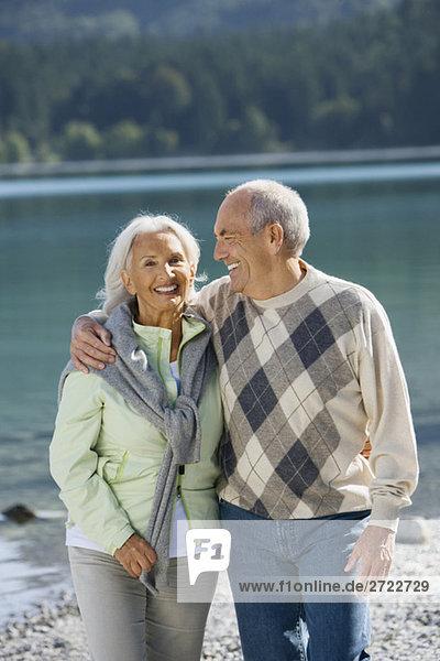 Deutschland  Bayern  Walchensee  Seniorenpaar am Seeufer  lächelnd
