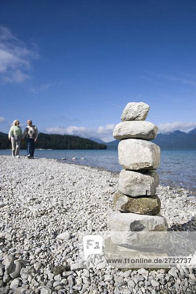 Germany  Bavaria  Walchensee  Senior couple taking a walk  stone pyramid in foreground