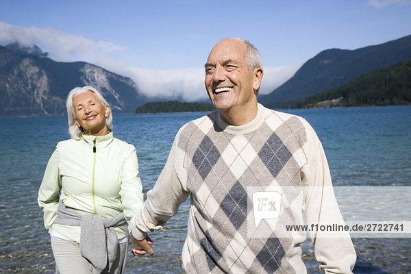 Deutschland  Bayern  Walchensee  Seniorenpaar geht Hand in Hand
