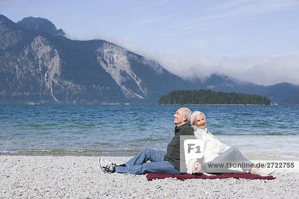 Germany  Bavaria  Senior couple relaxing on lakeshore  sitting back to back