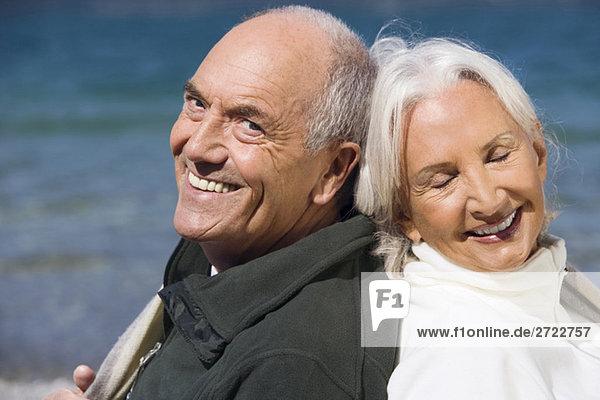 Deutschland  Bayern  Seniorenpaar am Seeufer  Rücken an Rücken  Nahaufnahme  Portrait