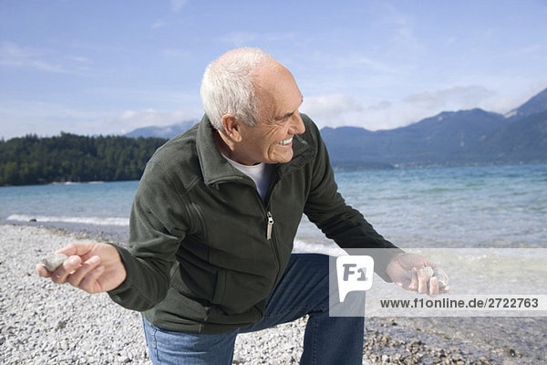 Senior man on lakeshore  skimming a stone