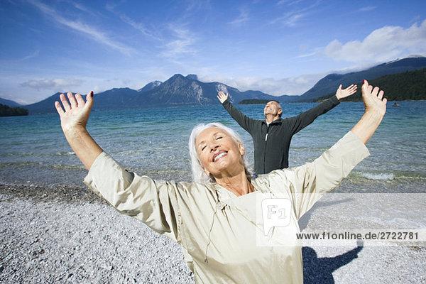 Deutschland  Bayern  Walchensee  Seniorenpaar am Seeufer  Arme ausgestreckt