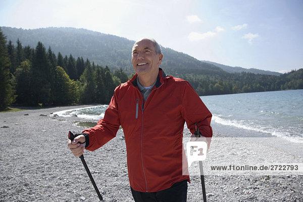 Senior Mann mit Nordic Walking Stöcken  lächelnd