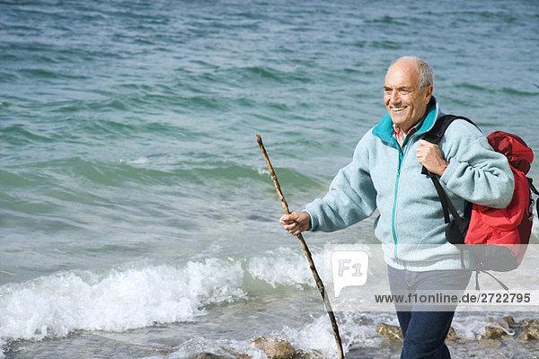 Senior Mann  der auf dem Wasser läuft.