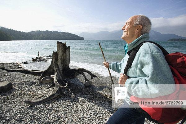 Senior Mann  der eine Pause am Seeufer macht.