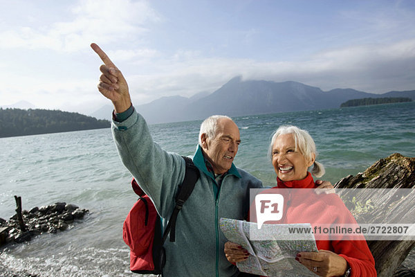 Senior couple with map  man pointing with finger