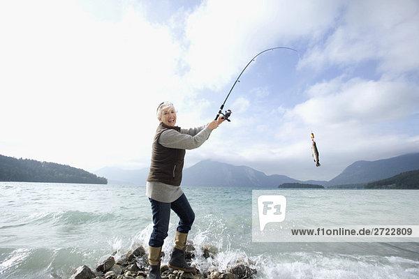 Seniorenfrau beim Angeln im See