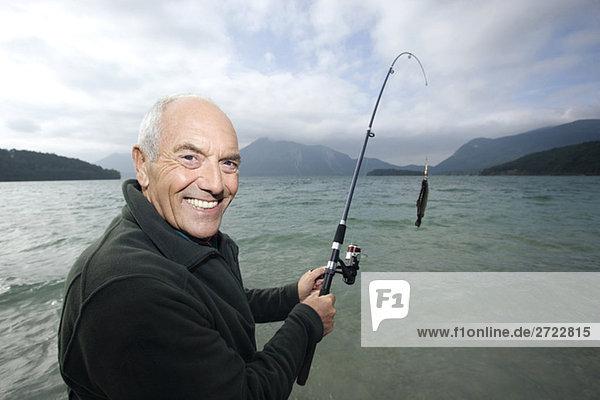 Senior Mann  der im See fischt.