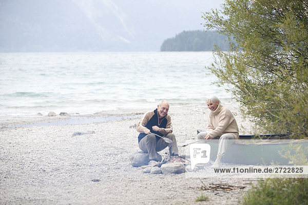 Germany  Bavaria  Walchensee  Senior couple sitting at campfire  grilling fish