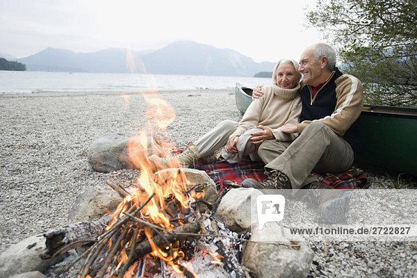 Germany  Bavaria  Walchensee  Senior couple sitting at campfire