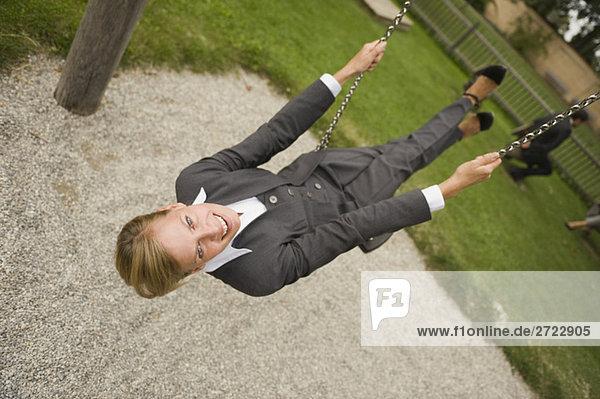 Deutschland  Geschäftsfrau auf Schaukel sitzend  Portrait
