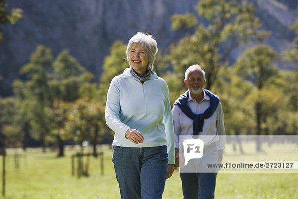 Austria  Karwendel  Senior couple walking across meadow