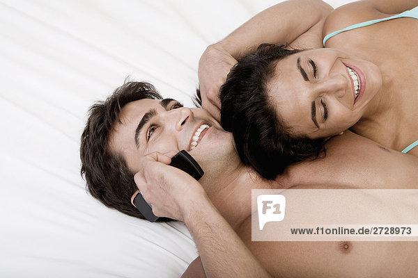 Junges paar auf einem Bett liegend