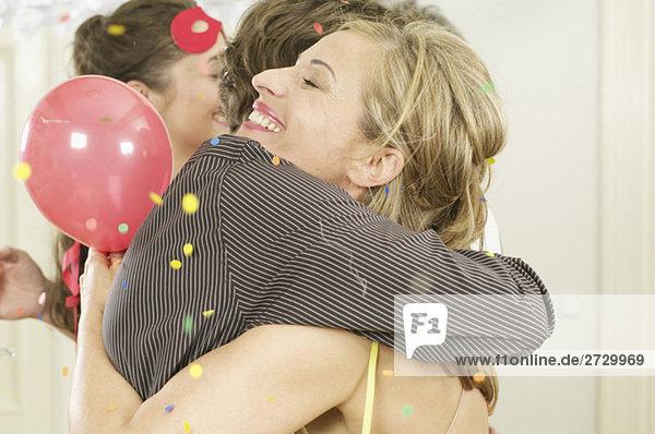 Frau und Mann umarmen sich auf einer Feier