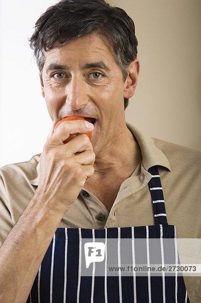 Älterer Mann isst eine Tomate  fully_released
