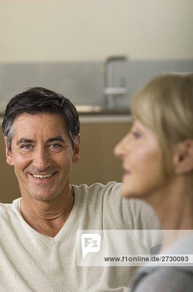 Älterer Mann lächelt in die Kamera  Frau im Vordergrund  fully_released