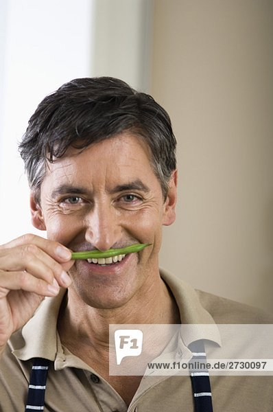 Älterer Mann riecht an einer grünen Bohne  fully_released