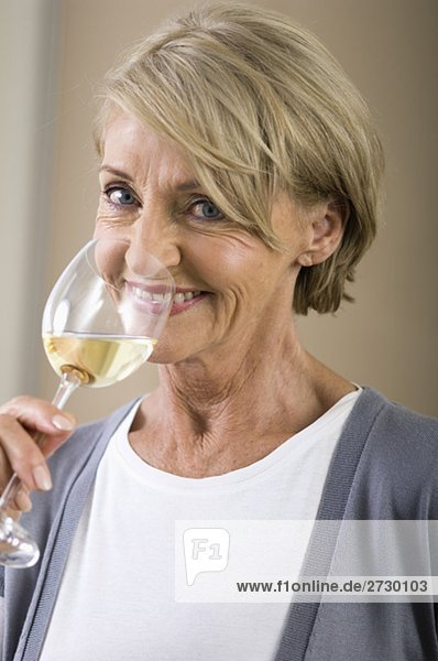 Alte Frau hält ein Glas Weiswein  fully_released