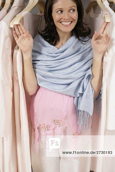 Schwangere Frau steht lächelnd zwischen Kleiderbügeln mit Kleidung  fully_released Schwangere Frau steht lächelnd zwischen Kleiderbügeln mit Kleidung, fully_released