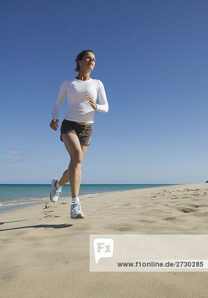 Junge Frau joggt am Strand entlang