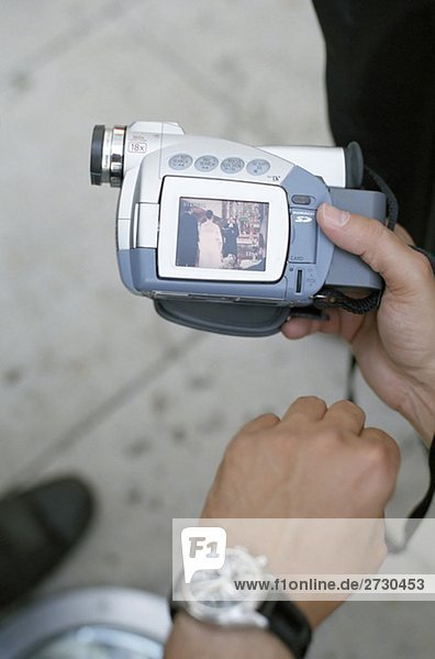 Man with a Digital Camera which shows a Picture of a Wedding - Technology
