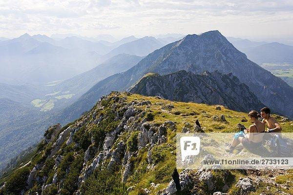 Paar sitzen oben auf Berg  Bayern  Deutschland