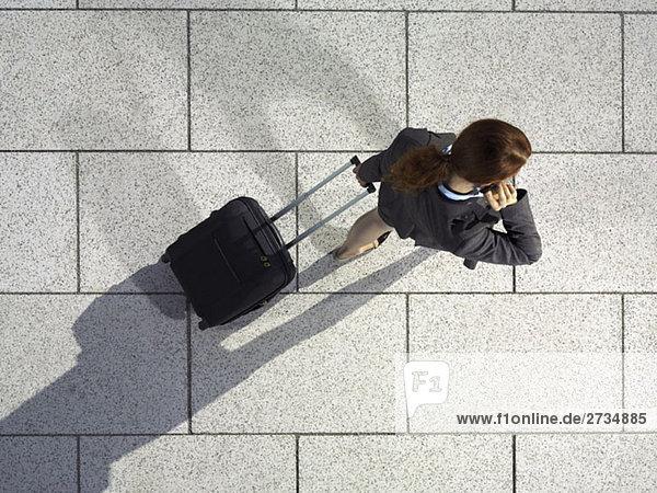 Eine Geschäftsfrau  die einen Koffer zieht und mit ihrem Handy spricht.