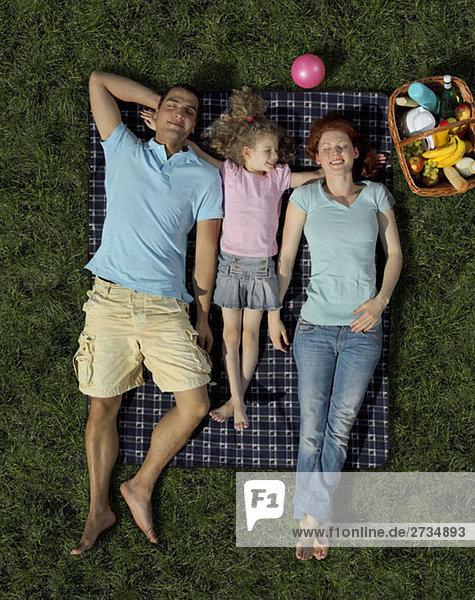 Eine Familie  die auf einer Decke auf Gras liegt.