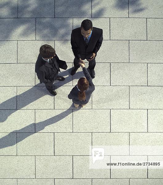 Drei Geschäftsleute beim Händeschütteln